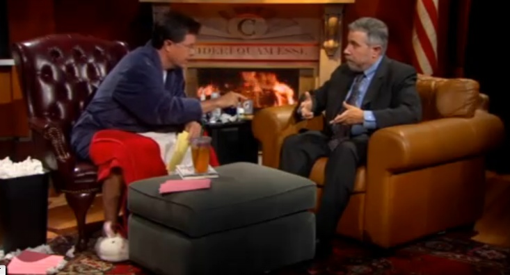 Stephen Colbert wearing the NASE's bunny slippers while interviewing Paul Krugman.